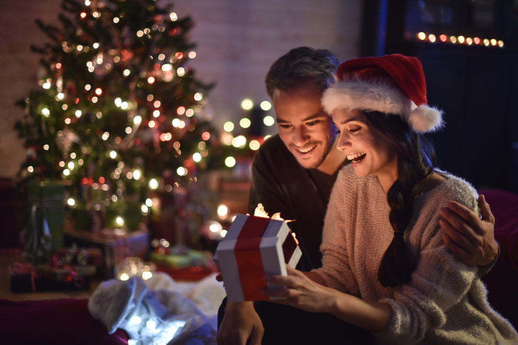 portrait of a young couple in their living room in christmas eve the young woman with santa hat on head smiled in opening his gift, a lit Christmas tree in the background