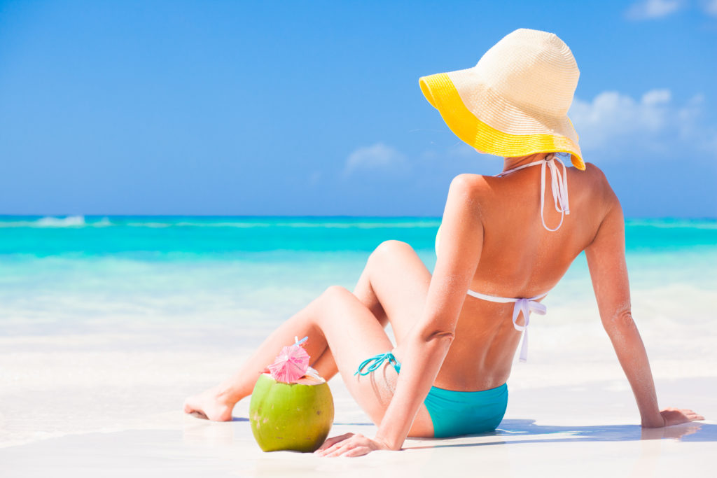 woman sitting on a beach with a hat drinking from a coconut element