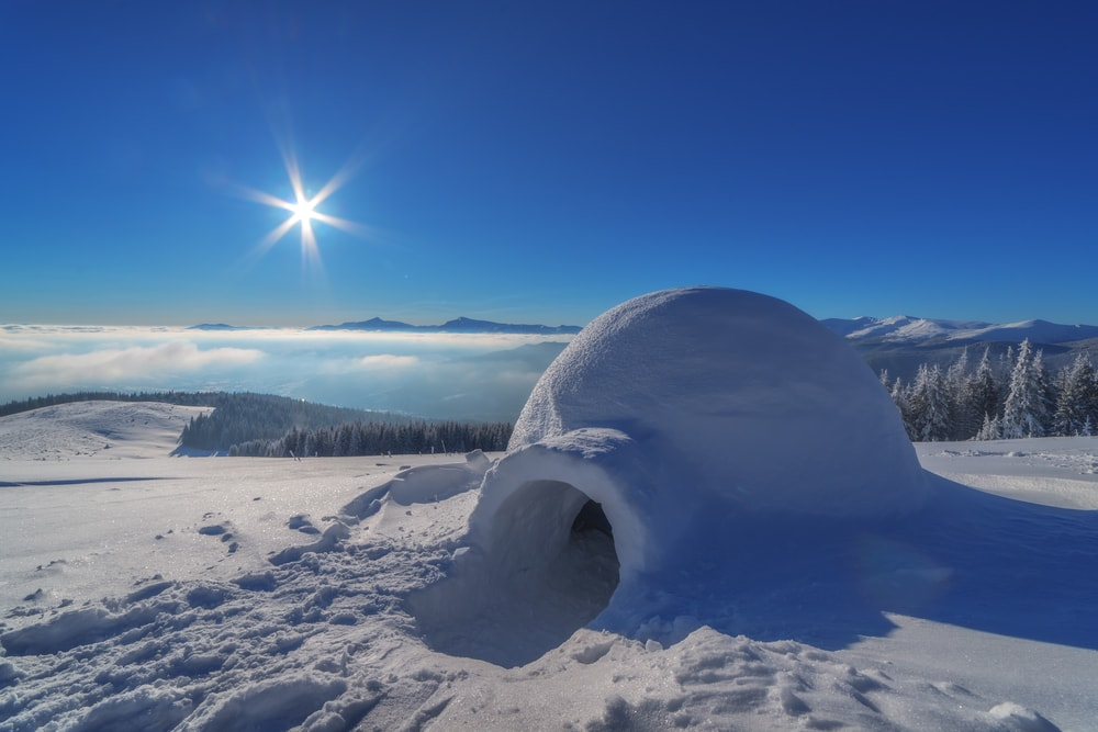 Igloo in the snow with the sun on the horizon for Element a prize for every season post