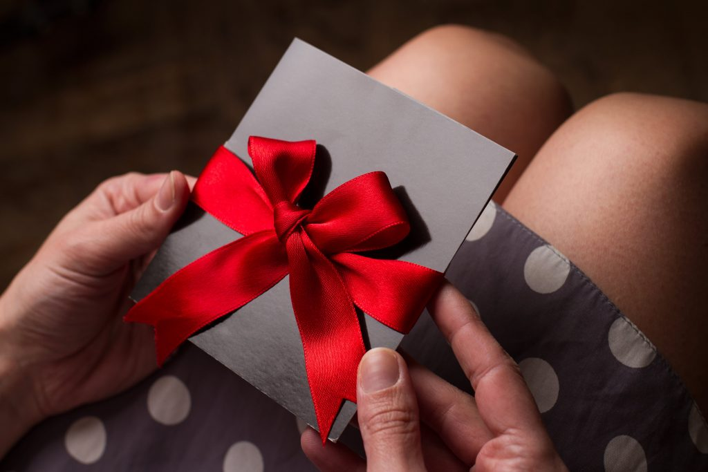 Close up of the hands of a woman with polka dress holding a black card with red ribbon above knees to illustrate Festive Vouchers and Rewards | Element