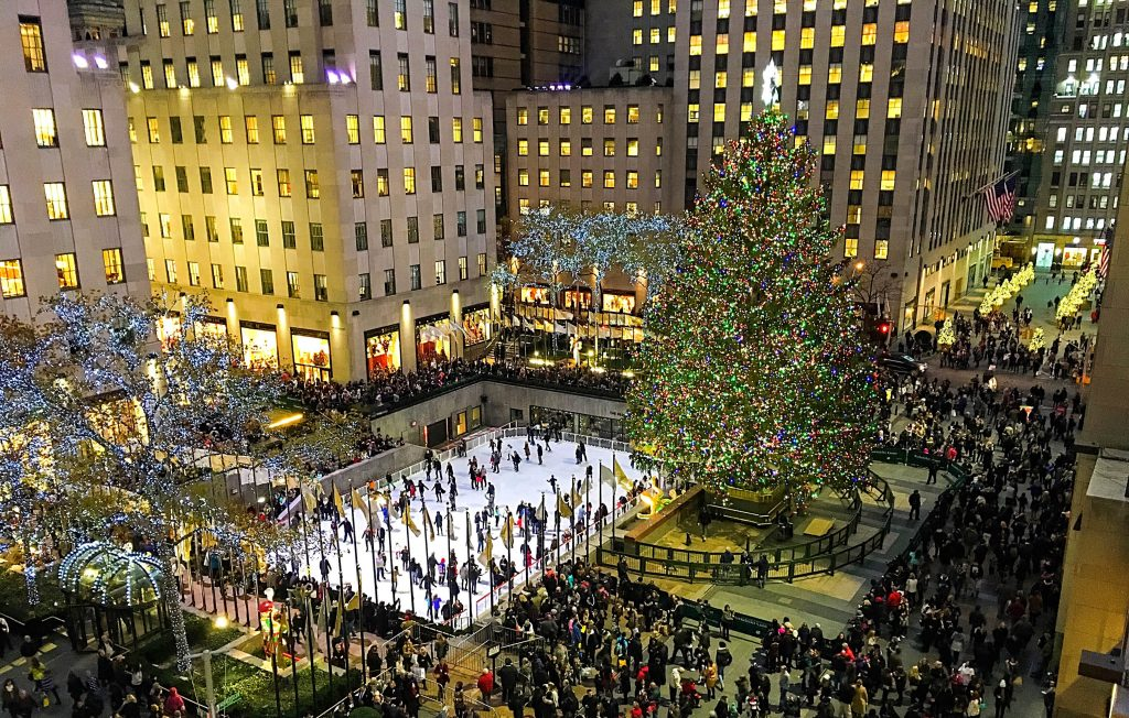 A scenic overview of the hustle and bustle of the holidays at night beneath the magnificent tree in Rockefeller Center to illustrate New York Christmas Incentives | Element